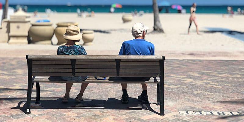 Elderly Couple Sitting in Bench on Beach